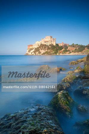 Alongside a picturesque millstone, atop a rocky promontory dominating the sea, rises the Castello di Falconara, Sicily, Italy, Mediterranean, Europe