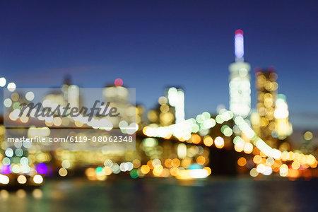 Defocussed view of Brooklyn Bridge and Lower Manhattan skyline at night, New York City, New York, United States of America, North America