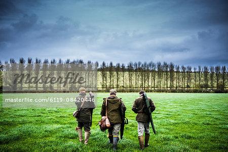Three guns walking towards a drive, Wiltshire, England, United Kingdom, Europe