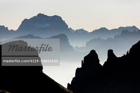 Mist on peaks of Dolomites and Monte Pelmo seen from Cima Belvedere at dawn, Val di Fassa, Trentino-Alto Adige, Italy, Europe