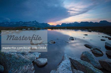 The lights of sunrise reflected in the alpine lake, Muottas Muragl, Samedan, Canton of Graubunden, Engadine, Switzerland, Europe