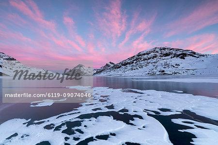 The frozen Lago Bianco framed by pink clouds at dawn, Bernina Pass, canton of Graubunden, Engadine, Switzerland, Europe