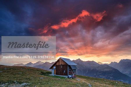 Wooden hut framed by fiery sky and clouds at sunset, Muottas Muragl, St. Moritz, Canton of Graubunden, Engadine, Switzerland, Europe