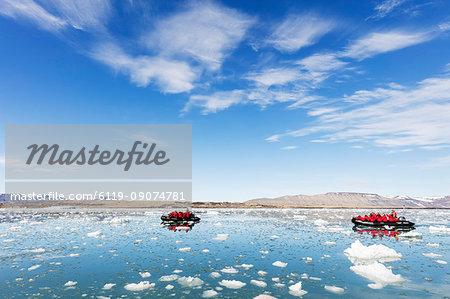 Tourist zodiac in an iceberg filled glacial lagoon, Spitsbergen, Svalbard, Arctic, Norway, Europe