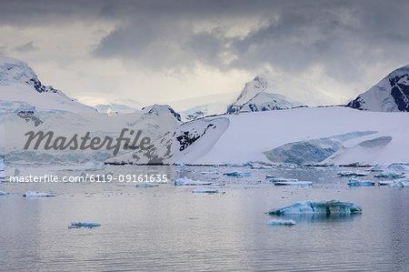 Spectacular mountains, glaciers and blue icebergs of Paradise Bay, water ripples, Graham Land, Antarctic Peninsula, Antarctica, Polar Regions