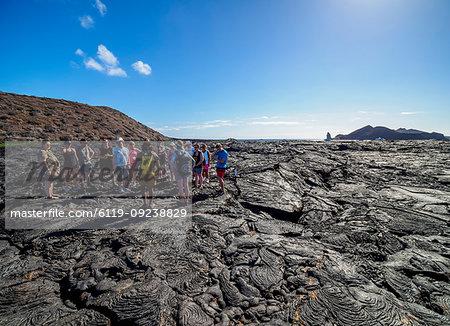 Tourists visiting Lava field in Sullivan Bay, Santiago (James) Island, Galapagos, UNESCO World Heritage Site, Ecuador, South America