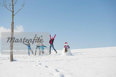 Family jumping on snow, Bavaria, Germany
