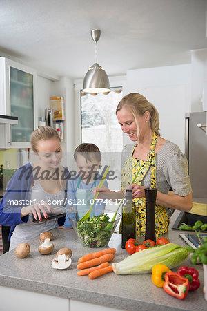 Mother and children preparing salad in kitchen, smiling