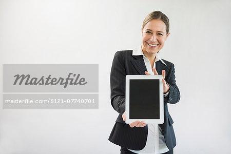 Portrait of businesswoman in black suit holding digital tablet, smiling
