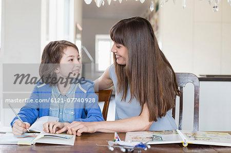 Mother helping daughter in homework, smiling