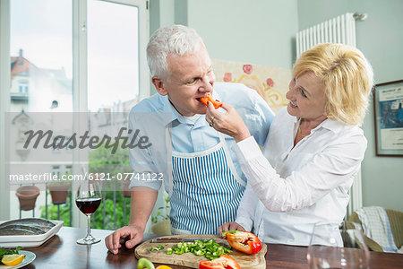 Mature woman feeding food to mature man, smiling