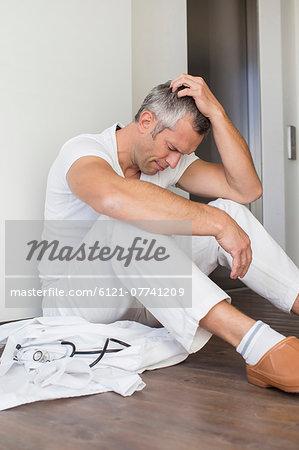 Unhappy doctor sitting on floor