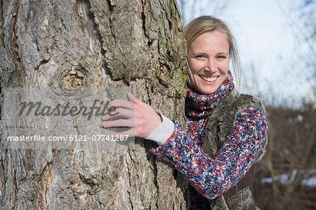 Portrait of woman hugging tree trunk, smiling, Bavaria, Germany