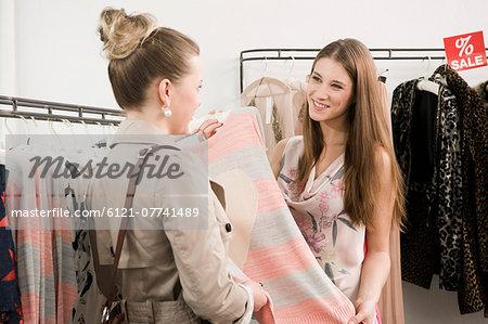 12e00dda3e Sales girl with customer in fashion store - Stock Photo - Masterfile ...