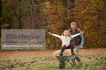 Father pushing happy daughter in wheelbarrow