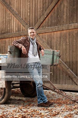 Smiling man leaning against trailer on farm