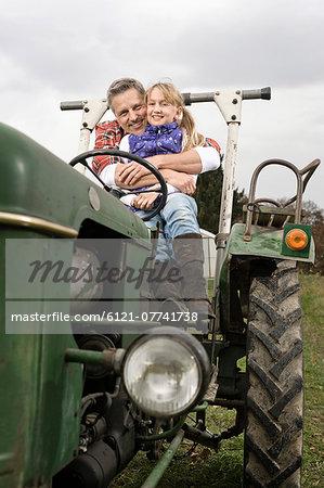 Farmer hugging daughter on tractor
