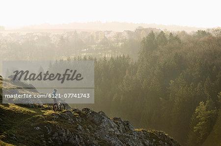 Young man mountainbiking at sunrise, Bavaria, Germany
