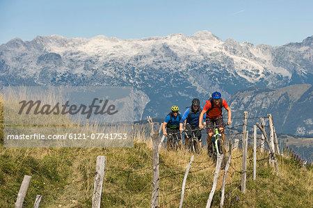 three mountain bikers on the way uphill, Matajur, Istria, Slovenia