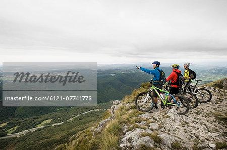 three mountain bikers looking at view, Vipava valley, Istria, Nanos, Slovenia