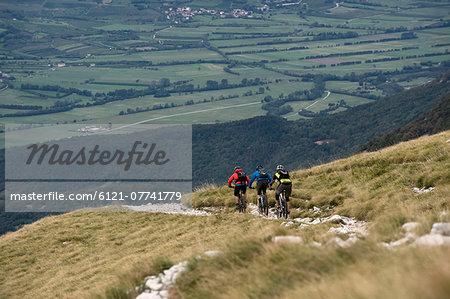 three mountain bikers on the way downhill, Vipava valley, Istria, Nanos, Slovenia