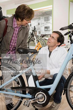 Salesman talking to woman beside bicycle