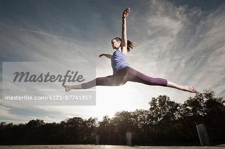 Woman jumpingmid air, Woerthsee, Bavaria, Germany