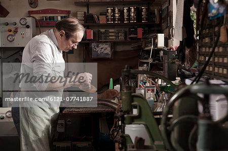 Cobbler working in workshop