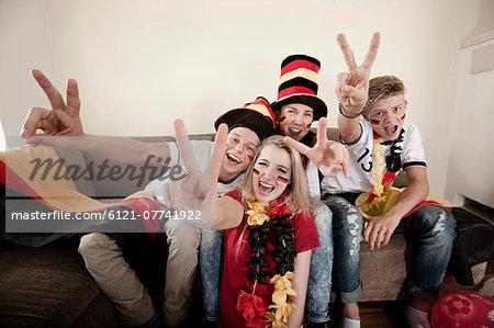 Teenage soccer fans posing in living room