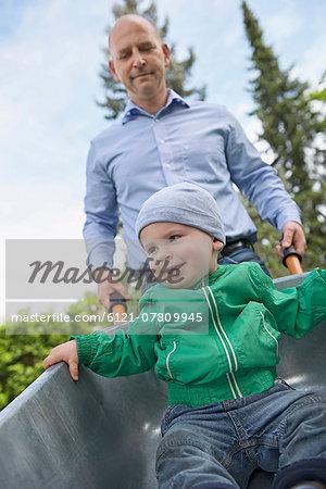 Father Pushing Baby Son In Wheelbarrow Stock Photo