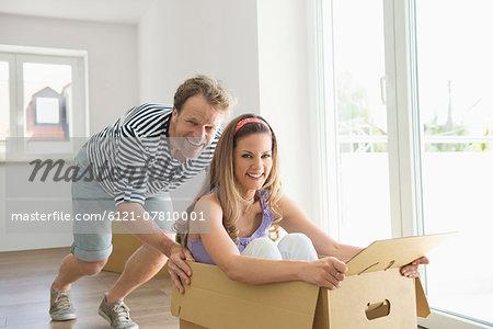Man pushing woman inside box new home