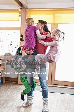 Female educator rampaging with three kids in kindergarten