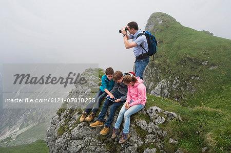 Father teenage kids in mountains iPad computer