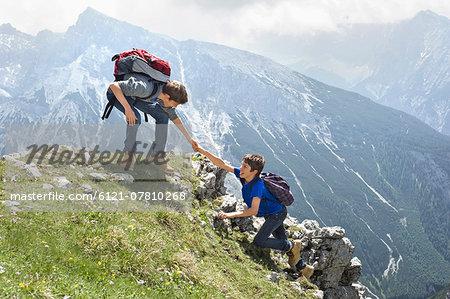 Teenage boys helping friend climbing in mountains