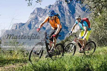 Men racing electic-mountainbikes mountain track
