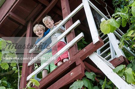 Young boys tree-house balcony ladder happy