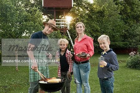 Mother father boys barbecue parents garden