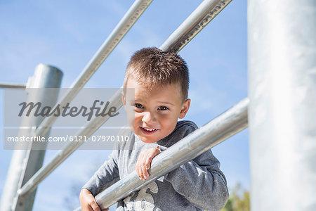 Small boy playing climbing frame playground
