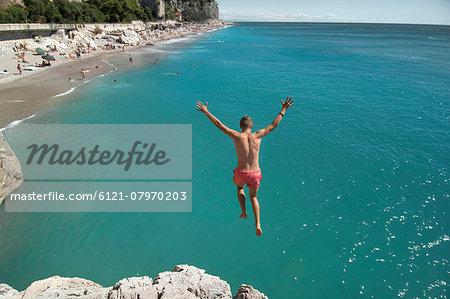 Boy holiday jump water ocean risk teenager