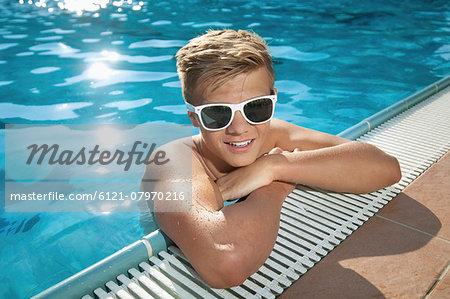 Close-up blond boy swimming pool sunglasses