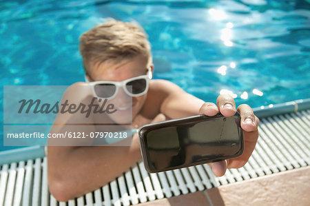 Close-up teenager boy swimming pool self-portrait