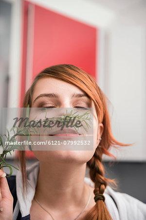 Woman smelling a twig of rosemary, Munich, Bavaria, Germany