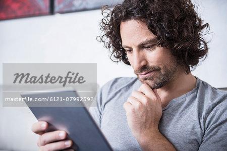 Man using a digital tablet at home, Munich, Bavaria, Germany