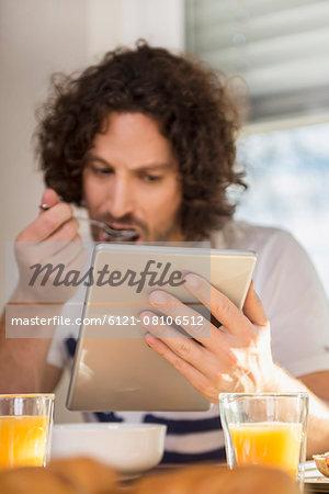 Mid adult man using a digital table at breakfast table, Munich, Bavaria, Germany