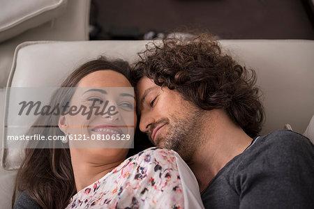Mid adult couple sleeping on sofa, Munich, Bavaria, Germany