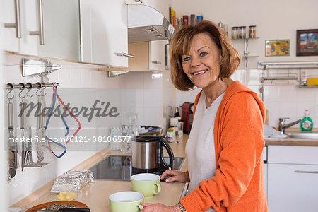 Senior woman preparing tea in the kitchen, Munich, Bavaria, Germany