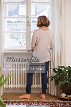 Rear view of senior woman looking through a window, Munich, Bavaria, Germany
