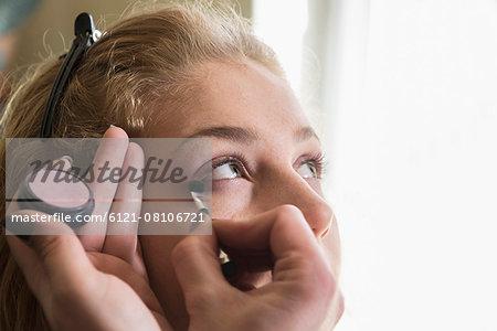 Makeup artist applying make up brush near eye, Munich, Bavaria, Germany