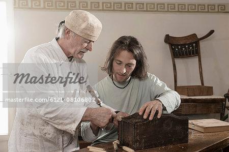 Restorer master explains apprentice something on an antique bone box, Bavaria, Germany