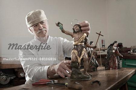 Senior sculptor works on a Jesus Christ statue at workshop, Bavaria, Germany